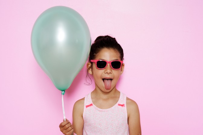 Beautiful and funny little girl holding colorful balloons and st
